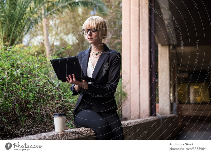 Young businesswoman sitting and using tablet stylish young browsing watching park fence female professional person beautiful attractive entrepreneur garden