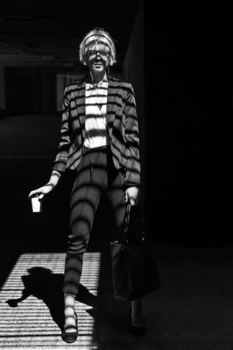 Fashionable woman with paper cup businesswoman stylish young window shutters shadows looking at camera standing lines stripes female professional person