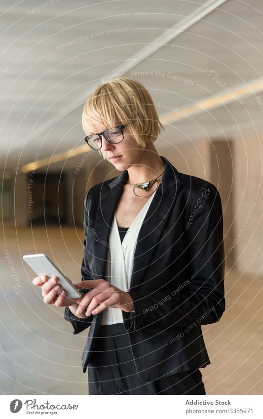 Stylish businesswoman browsing smartphone mobile connection watching stylish young confident hall female professional person beautiful attractive entrepreneur
