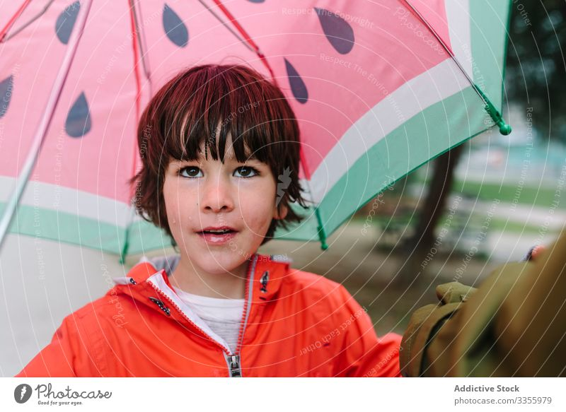 Cute child with colorful umbrella looking at camera in park alley rain season funny water wet dirt childhood mud autumn game active weather rubber boots