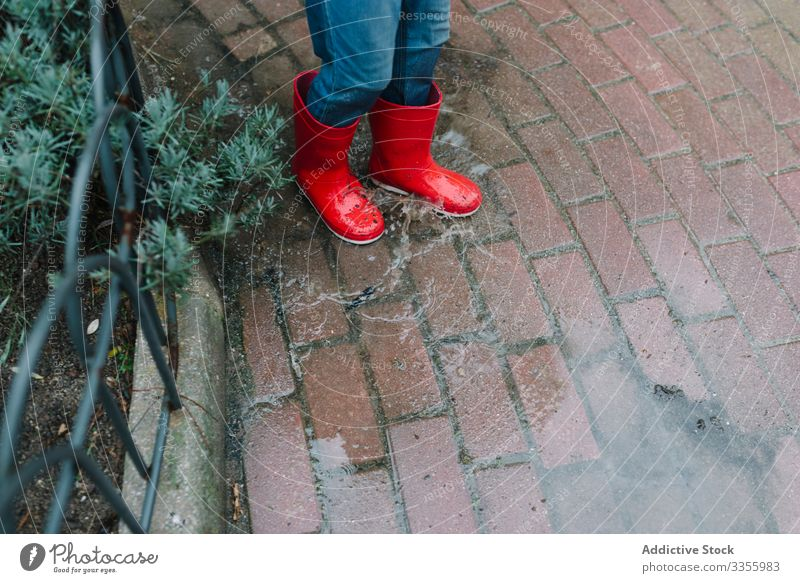 Active kid jumping in puddle in park alley child messy season funny water wet dirt childhood weather mud autumn game active rubber boots raincoat botanical