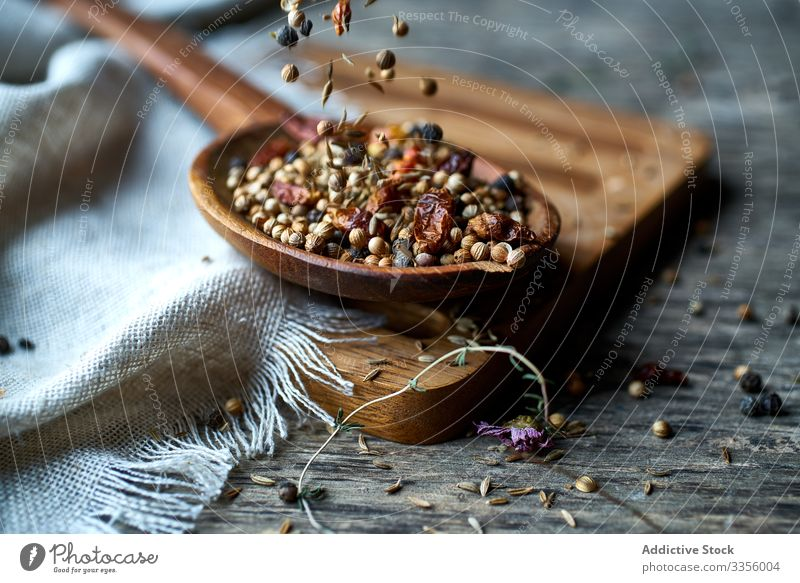 Dry mix of spices and dried berries in spoon on table fragrant herb harvest ripe natural pepper seasoning healthy edible wooden gathering heap ingredient