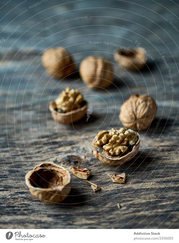 Ripe half peeled walnuts at wooden table ripe healthy edible filbert harvest gathering heap ingredient natural organic raw cracked seed food snack tasty