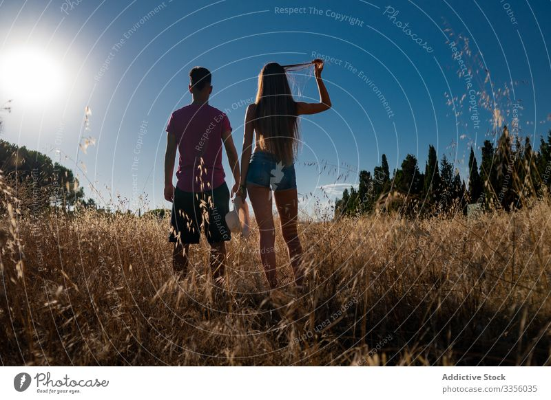 Playful young male standing with female in field with hat in hand friend play nature travel adventure activity together playful sky freedom journey relax
