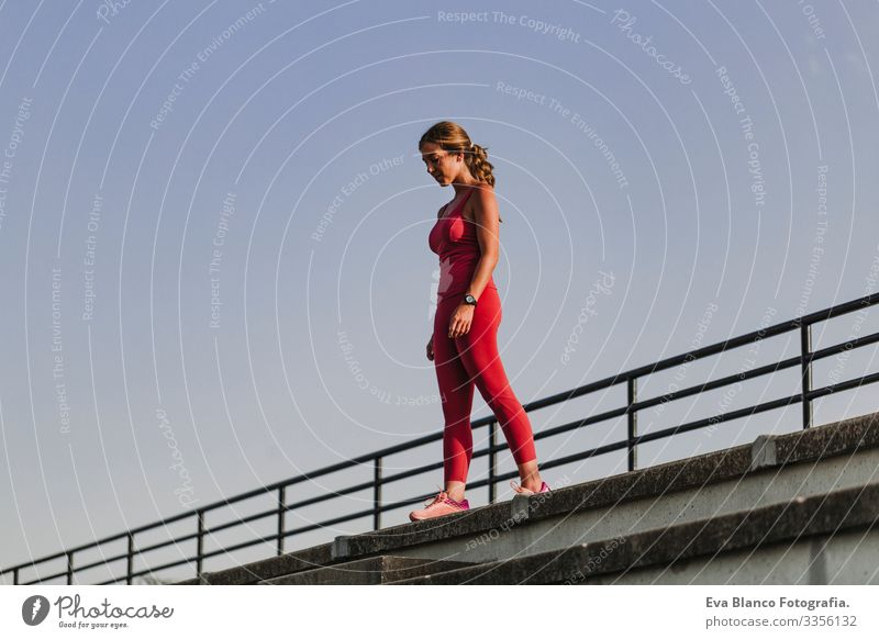 Fitness woman on stadium ready to practice sport. Wearing Red sport clothes. healthy lifestyle concept. Sunset at summer Body Woman Stadium Wellness Athlete
