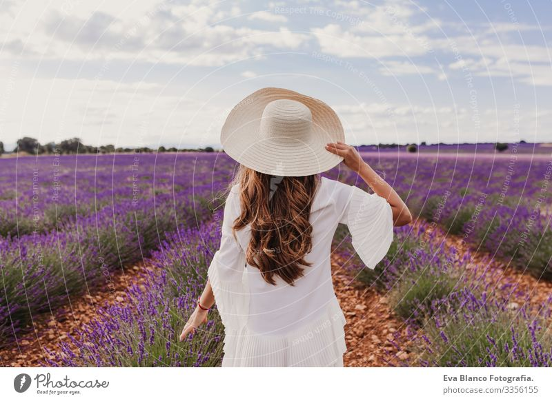 charming Young woman with a hat and white dress in a purple lavender field at sunset. LIfestyle outdoors. Back view Sunset Meadow Beauty Photography Joy