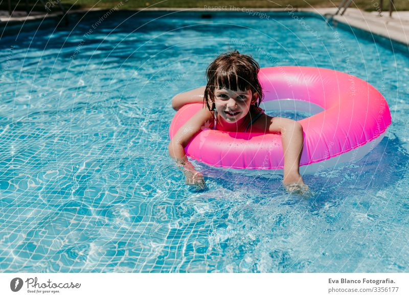 beautiful kid girl floating on pink donuts in a pool. Wearing sunglasses and smiling. Fun and summer lifestyle Action Swimming pool Beauty Photography