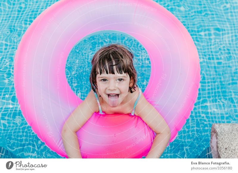 beautiful kid girl floating on pink donuts in a pool. Smiling. Fun and summer lifestyle Action Swimming pool Beauty Photography Exterior shot