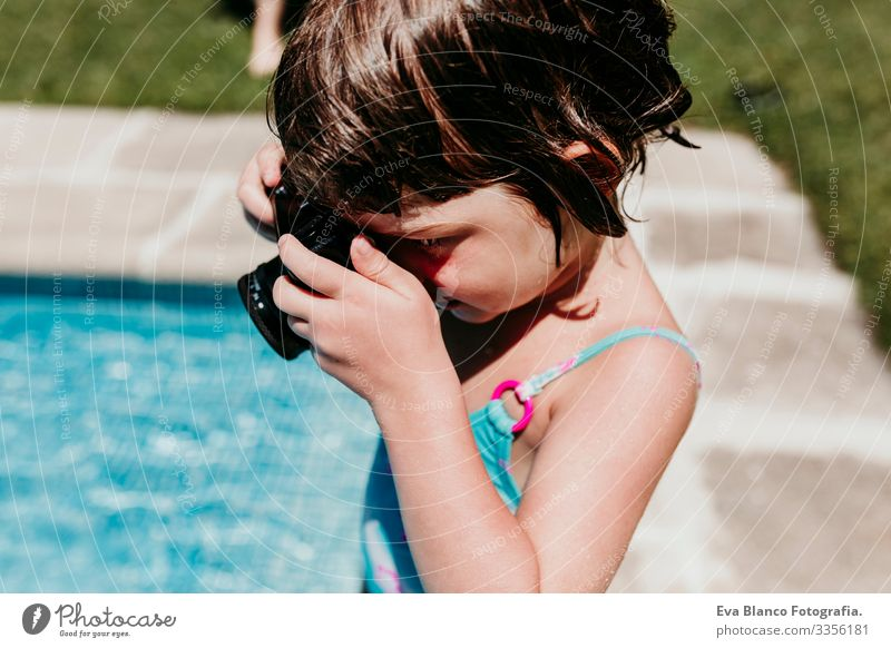 beautiful kid girl taking a picture with old vintage camera in a pool. Smiling. Fun and summer lifestyle Action Swimming pool Beauty Photography Exterior shot