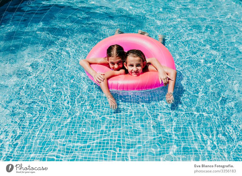 two beautiful teenager girls floating on pink donuts in a pool. smiling. Fun and summer lifestyle Action Swimming pool Exterior shot Youth (Young adults) Girl