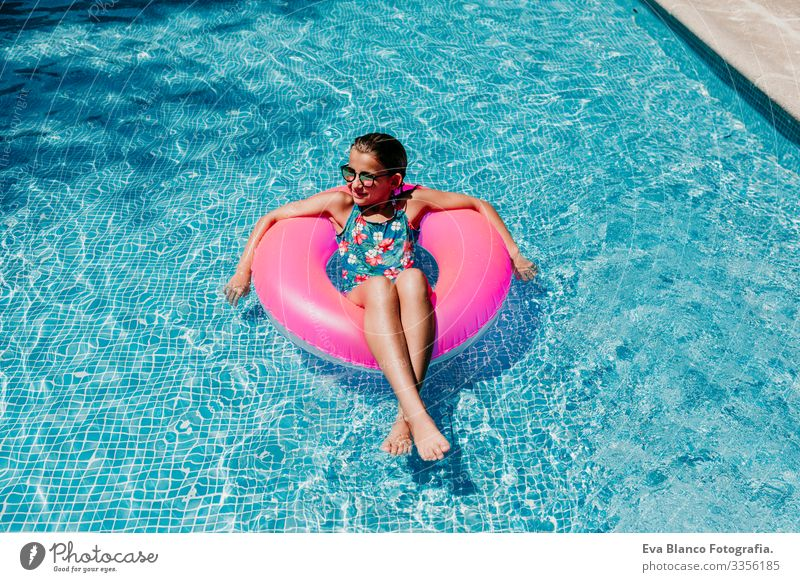 beautiful teenager girl floating on pink donuts in a pool. Wearing sunglasses and smiling. Fun and summer lifestyle Action Swimming pool Beauty Photography