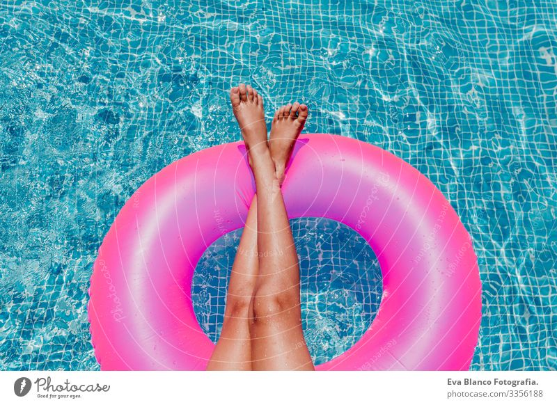 unrecognizable teenager girl floating on pink donuts in a pool. Wearing sunglasses and smiling. Fun and summer lifestyle Action Swimming pool Beauty Photography