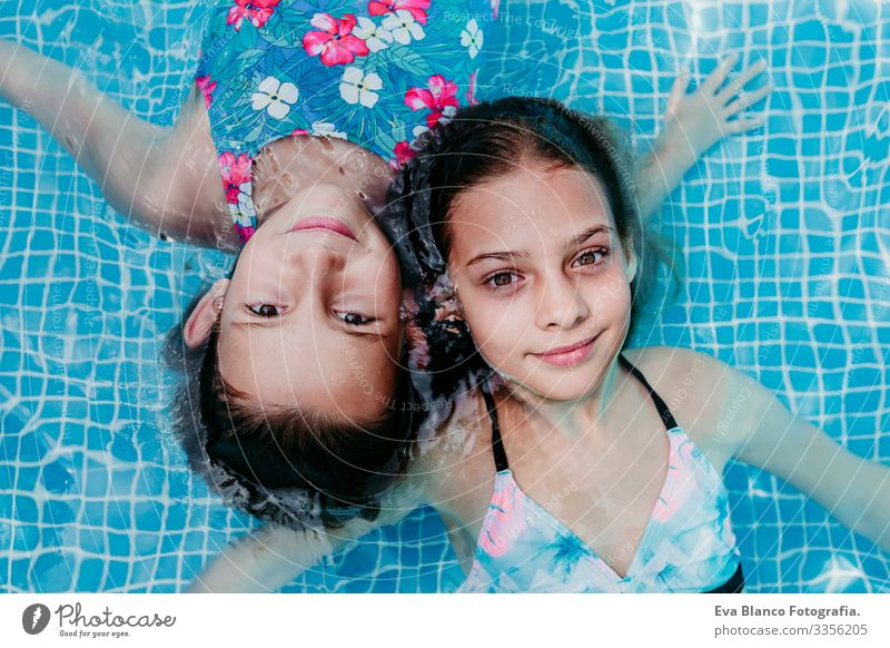 two beautiful teenager girls floating in a pool and looking at the camera. Fun and summer lifestyle Action Swimming pool Exterior shot Youth (Young adults) Girl
