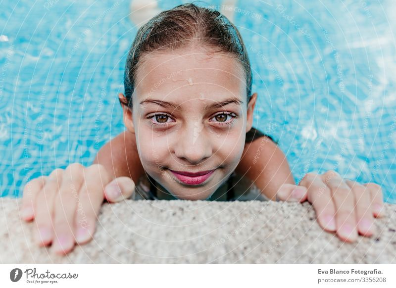 beautiful teenager girl floating in a pool and looking at the camera. Fun and summer lifestyle Action Swimming pool Beauty Photography Exterior shot