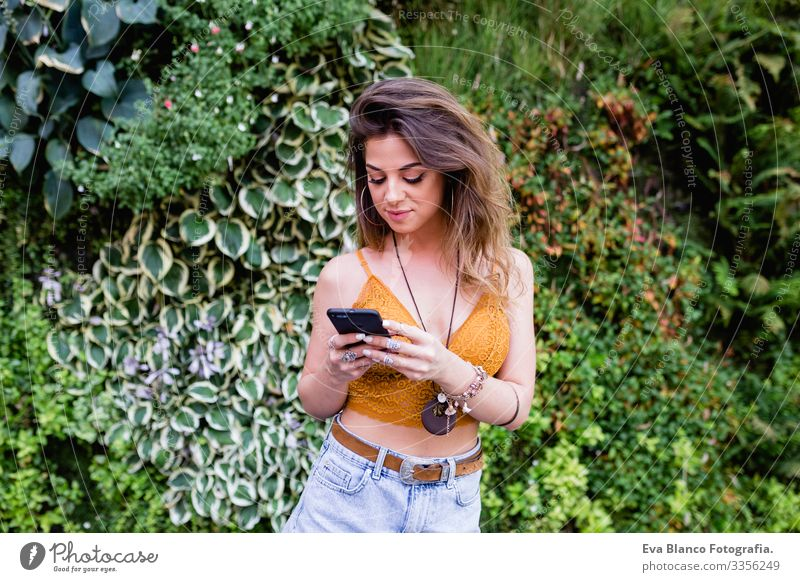 young blonde beautiful woman at the street using mobile phone and smiling. Lifestyle outdoors. Summertime, Green background Smart Town Happy Human being Smiling