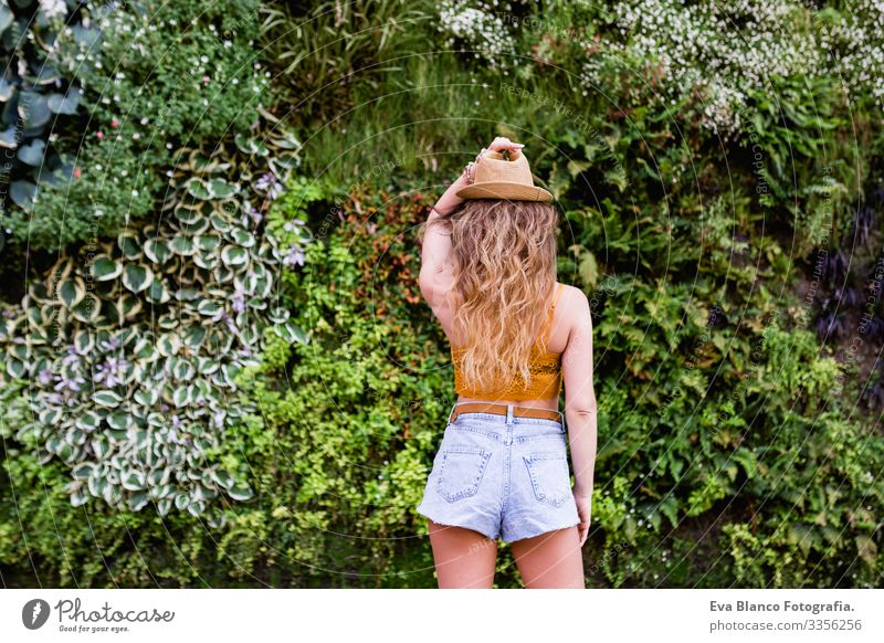 portrait of a young blonde beautiful woman at the street smiling. Green vegetation background. Lifestyle outdoors. Summertime Modern Hip & trendy Eroticism