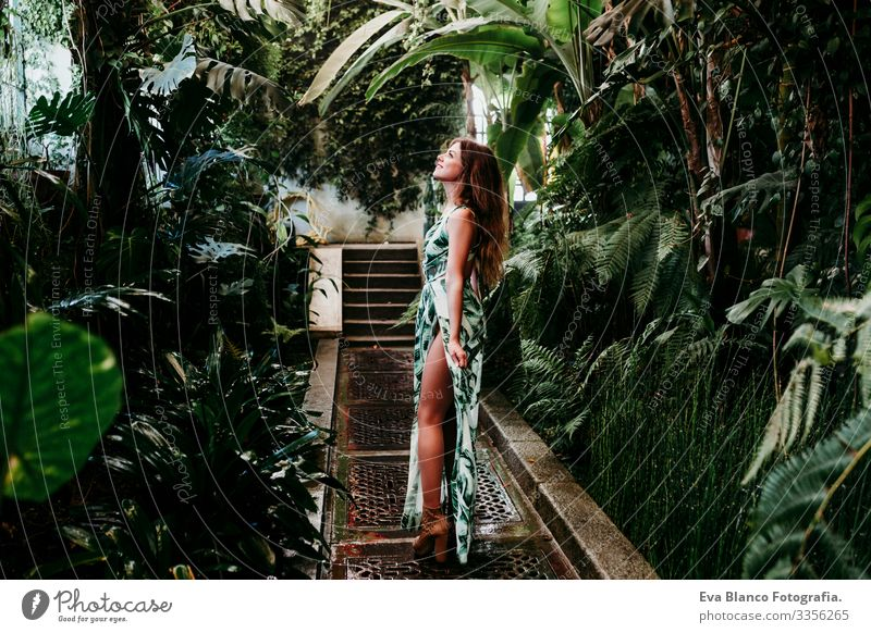 portrait of beautiful blonde young woman smiling at sunset in a green house surrounded by tropical plants. Happiness and lifestyle concept Caucasian toothy Cute
