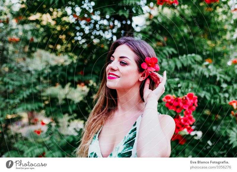 portrait of beautiful blonde young woman smiling at sunset. Playing with red flowers. Happiness and lifestyle concept outdoors Caucasian toothy Cute Happy Girl