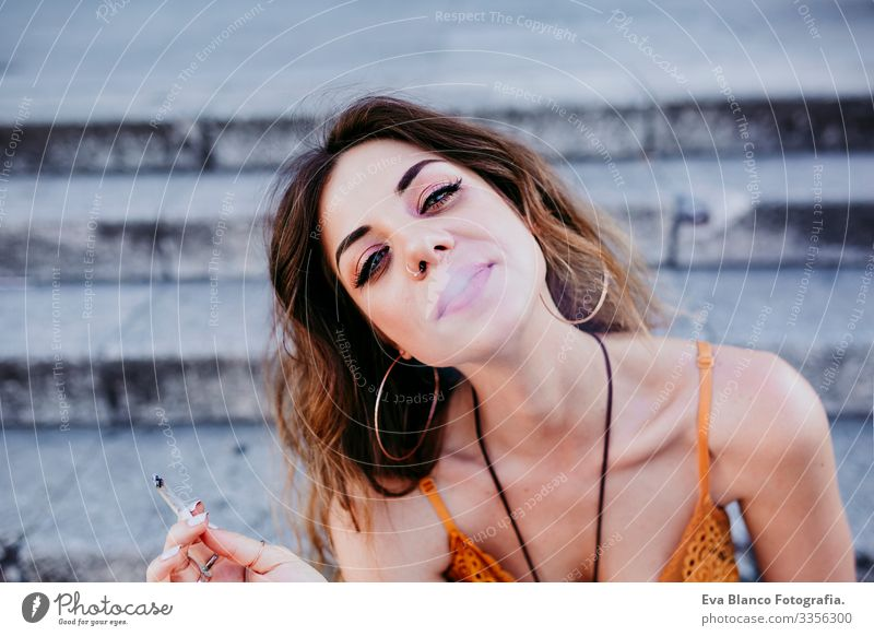 Beautiful young caucasian woman sitting on stairs at the city street on a sunny day and smoking a cigarette. Urban lifestyle and smoking concept. close up view