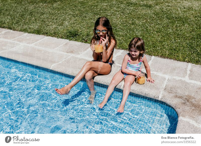 two beautiful sisters at the pool drinking orange juice, summer time Child Family & Relations two sisters Friendship Together To enjoy Floating Donut Caucasian