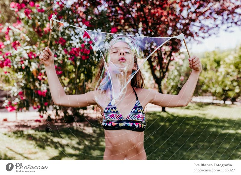cute kid girl playing outdoors with bubbles, summertime Lifestyle Swimming pool Vacation & Travel Sun Summer healthy Caucasian Smiling Blue enjoyment Swimwear