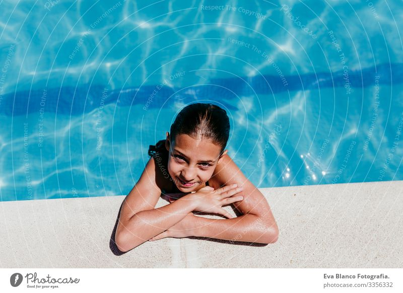 beautiful kid girl at the pool, summer time Sunlight Day Exterior shot young Swimwear water swimming enjoyment kids cheerful Playful Caucasian Blue healthy Cute