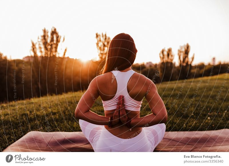 young beautiful asian woman doing yoga in a park at sunset. Yoga and healthy lifestyle concept. Back view Youth (Young adults) Woman Summer Happy enjoyment