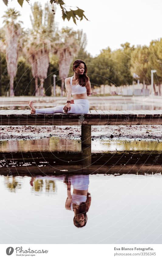 young beautiful asian woman doing yoga in a park. Sitting on the bridge with reflection on the water lake. Yoga and healthy lifestyle concept Practice