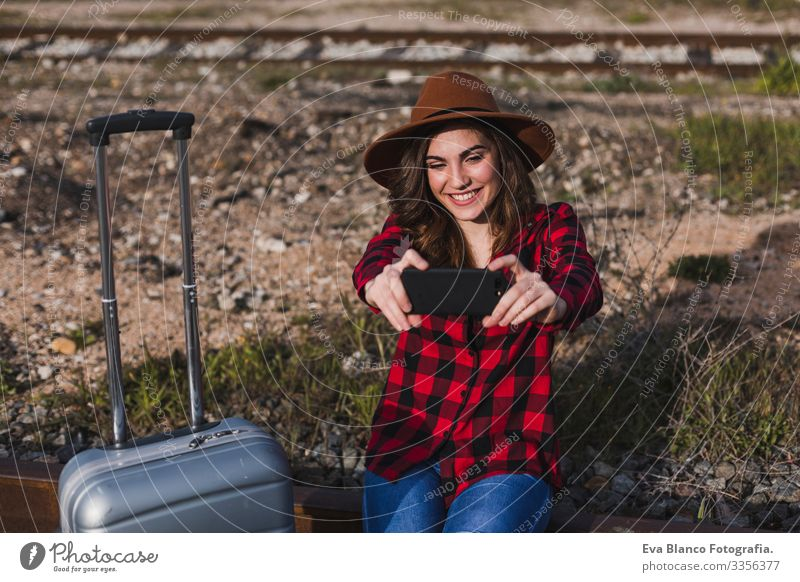 young beautiful woman wearing casual clothes, walking by the railway with suitcase and mobile phone and smiling. Outdoors lifestyle. Travel concept. She is taking a picture or selfie