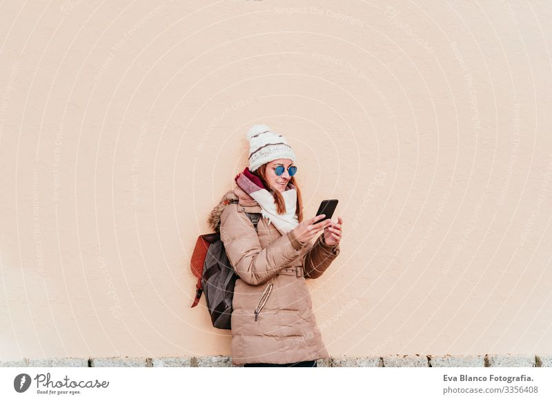 woman using mobile phone over yellow wall background. Technology and winter concept Woman Exterior shot City Wall (building) Winter Cellphone Yellow