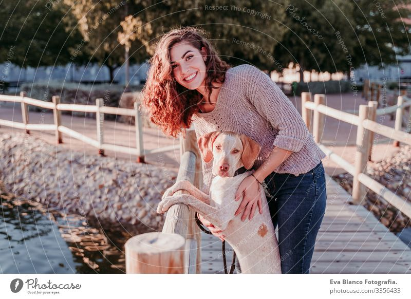 young woman and her dog outdoors walking by a wood bridge in a park with a lake. sunny day, autumn season Portrait photograph Woman Dog Park