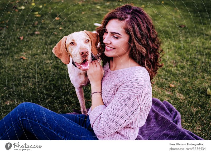 young woman with her dog at the park. she is hugging the dog. autumn season Portrait photograph Woman Dog Park Youth (Young adults) Exterior shot Love Pet owner