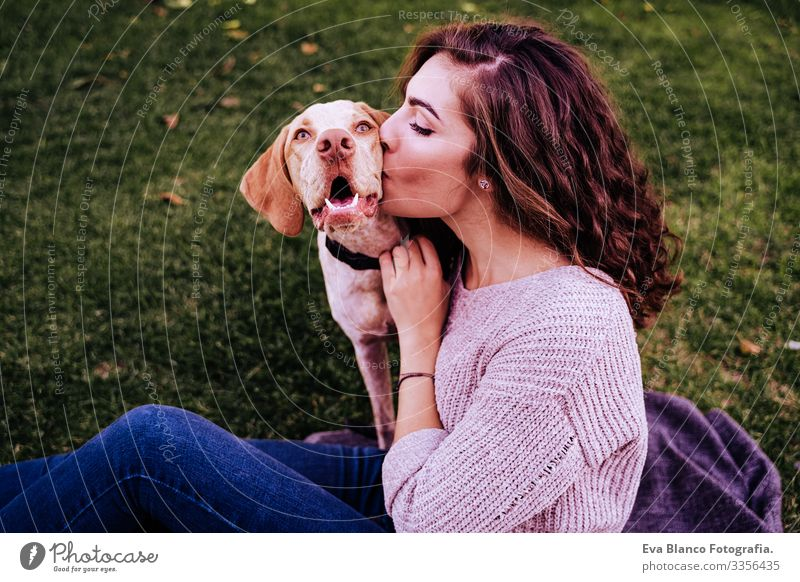 young woman with her dog at the park. she is kissing the dog. autumn season Portrait photograph Woman Dog Park Youth (Young adults) Exterior shot Love Pet owner