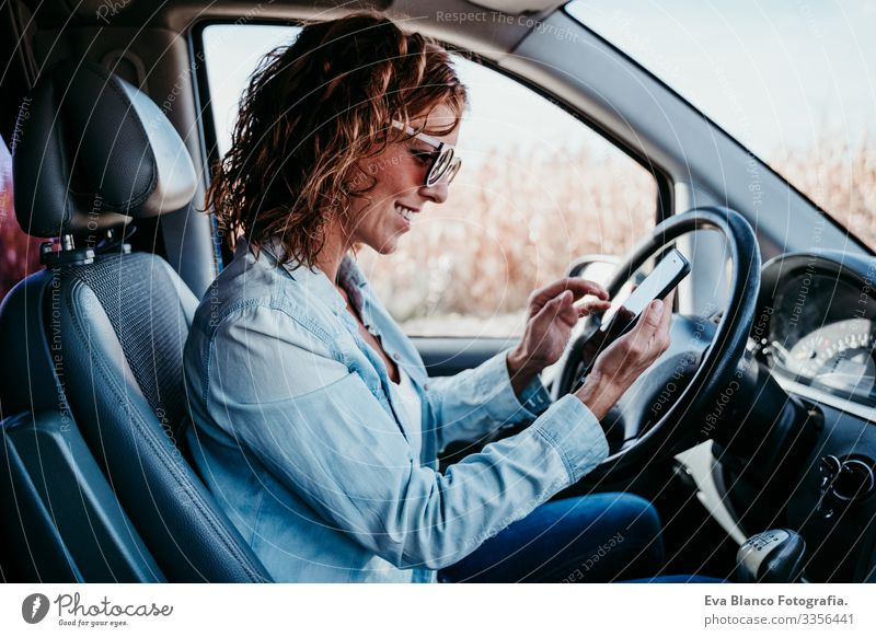 young beautiful woman using mobile phone in a car. travel concept Cellphone Technology Woman Youth (Young adults) Driving Car Sunbeam Sunglasses
