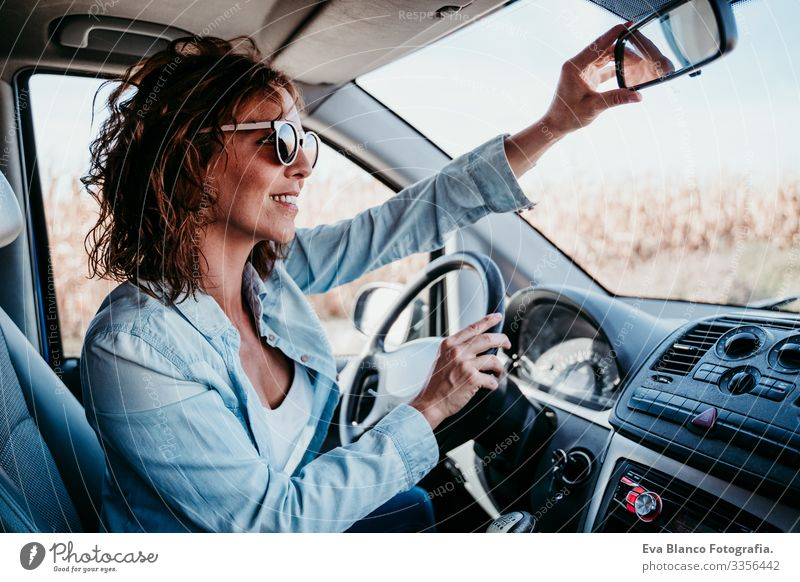 young beautiful woman driving a car and adjusting rear mirror. travel concept Woman Youth (Young adults) Driving Car Sunbeam Sunglasses Vacation & Travel