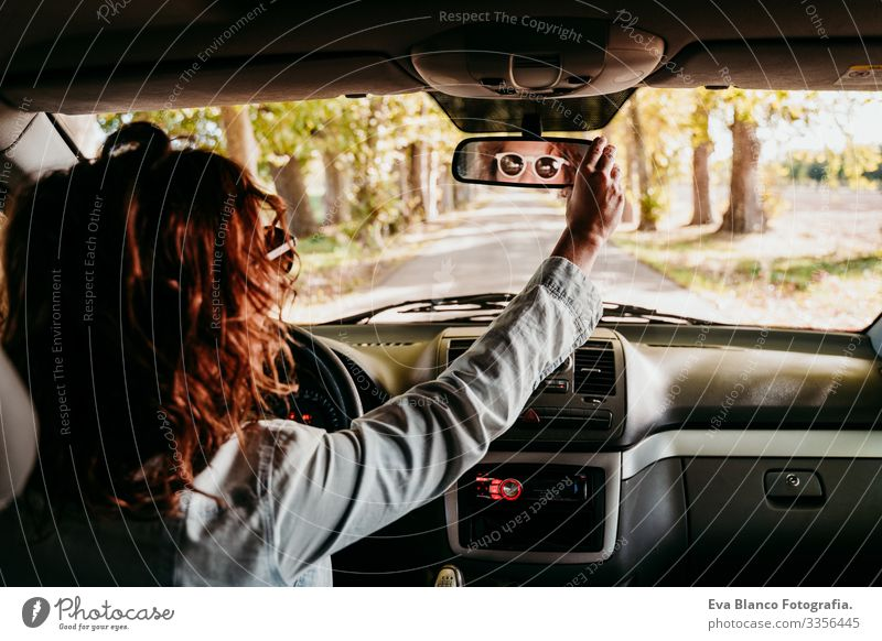 young beautiful woman driving a car. travel concept. view from inside. path of trees road Woman Youth (Young adults) Driving Car Sunbeam Sunglasses