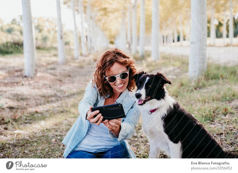 woman and beautiful border collie dog sitting in a path of trees outdoors. woman taking a selfie with mobile phone Woman Dog Selfie Cellphone Exterior shot