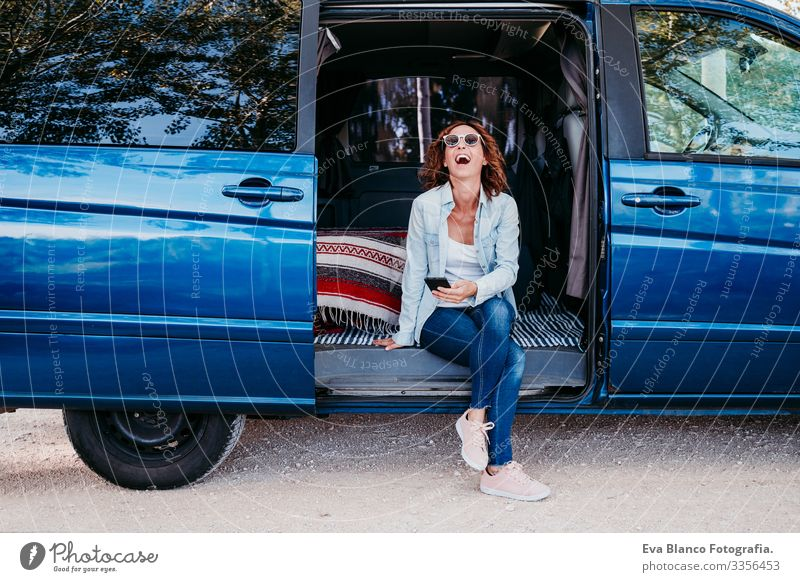 happy woman sitting in a blue van and having fun. travel concept Woman Happy Laughter Van Car Vacation & Travel Cellphone enjoying Joy Exterior shot Sit Resting