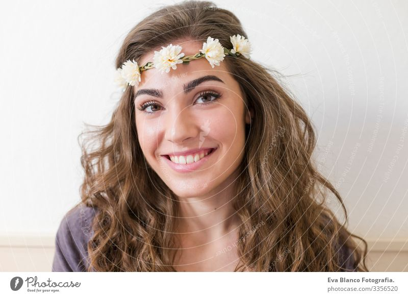 portrait of a young beautiful woman wearing a flowers wreath. She is smiling, indoors. Lifestyle. Horizontal view Head Elegant Amazing Aromatic Considerate