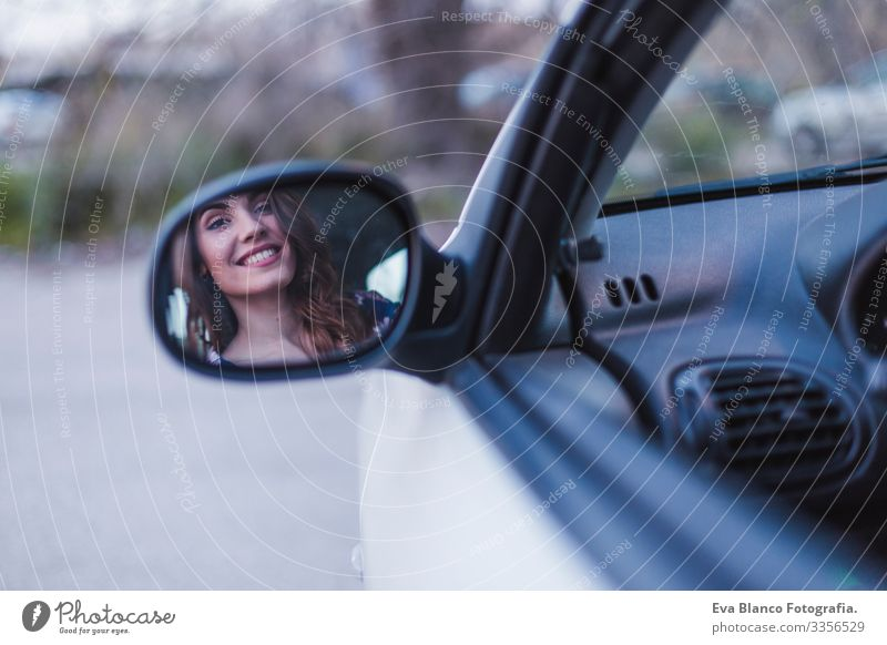 Young woman driving a car in the city. Portrait of a beautiful woman in a car, looking out of the window and smiling. Reflection in rear mirror. Travel and vacations concepts