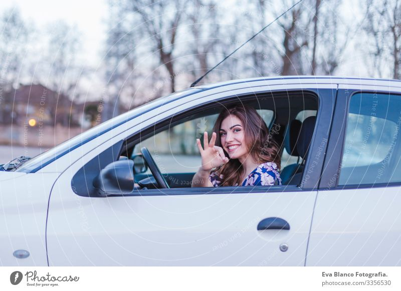 Young woman driving a car in the city. Portrait of a beautiful woman in a car, looking out of the window and smiling. Travel and vacations concepts