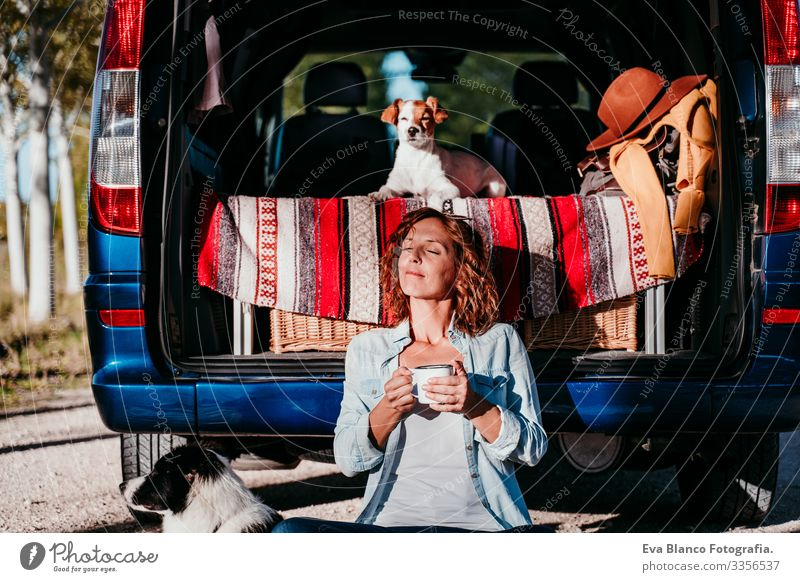 young beautiful woman drinking coffee or tea camping outdoors with a van and her two dogs. Travel concept Drinking Tea Coffee Teapot Woman Dog border collie Van