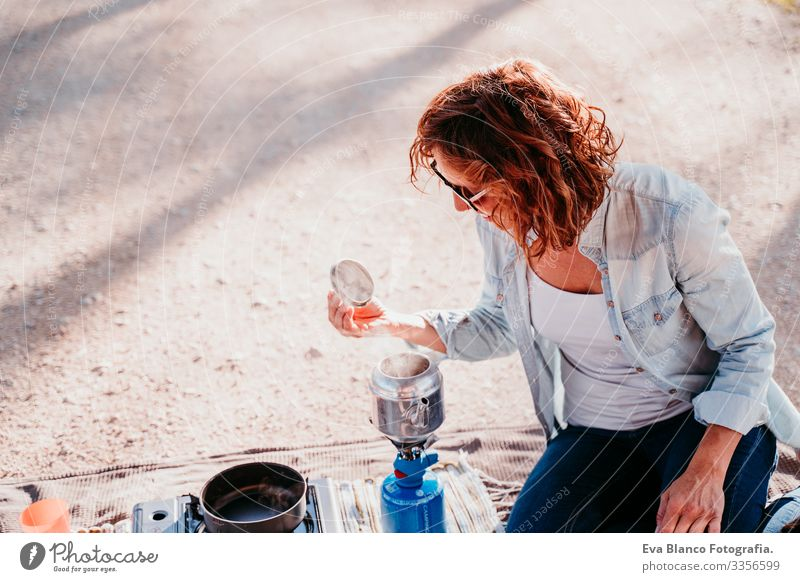 young woman preparing tea with pot and stove outdoors. camping concept Youth (Young adults) Woman Camping Pot Stove & Oven Sunset Hot Tea Teapot Coffee Day