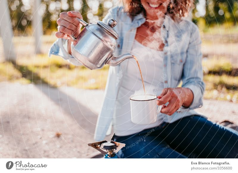 young woman pouring tea with pot outdoors. Using stove. camping concept Youth (Young adults) Woman Camping Pot Stove & Oven Sunset preparing Hot Tea Teapot