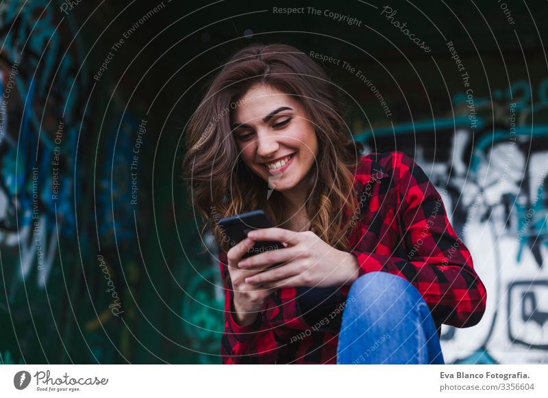 young beautiful woman using mobile phone. Urban graffiti background. Outdoors lifestyle.Technology Town Hat Beautiful Stand Attractive Mobile Fence Skyline