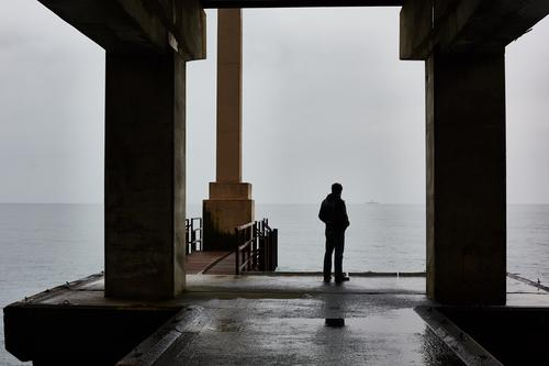 Man stands alone on a pier of sea in bad weather. Freedom Adults Fog Think Sadness Loneliness Considerate jetty Dramatic alone guy calm sea cold temperature