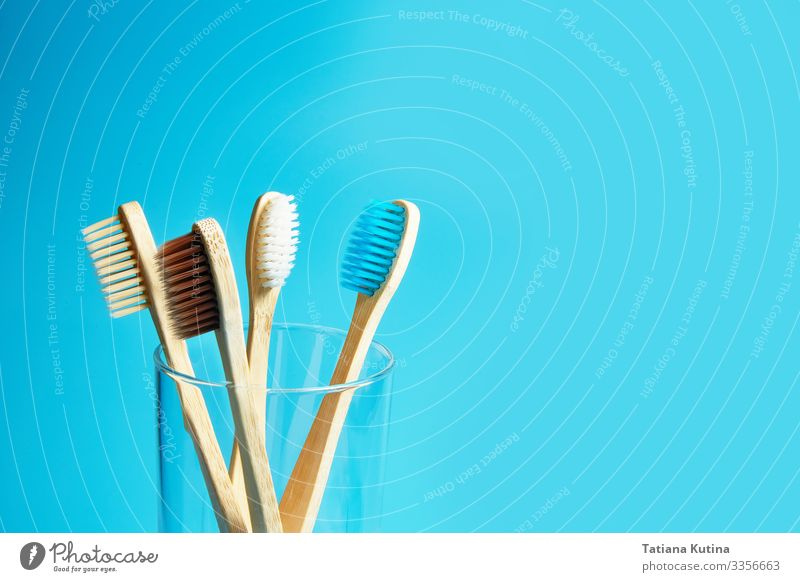 Wooden toothbrushes with a glass cup on a blue background. Lifestyle Medical treatment Wellness Bathroom Environment Nature Packaging Toothbrush Plastic Free