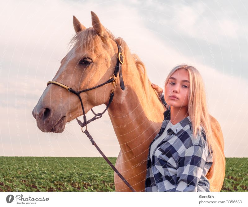 young blonde girl with a beige horse Style Beautiful Face Summer Human being Woman Adults Friendship Hand Nature Animal Village Clothing Shirt Blonde Horse Near
