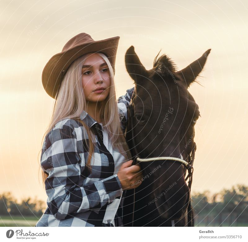 girl dressed in a cowboy hat with a horse at sunset on the ranch Style Face Summer Human being Woman Adults Hand Nature Plant Animal Sky Grass Meadow Village