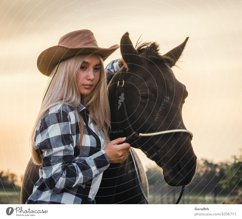 young girl dressed in a cowboy hat with a horse at sunset Style Face Summer Human being Woman Adults Hand Nature Plant Animal Sky Grass Meadow Village Clothing